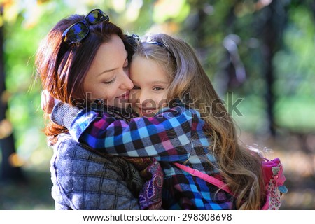 Young happy mother and little daughter hugging at autumn park background  - stock photo
