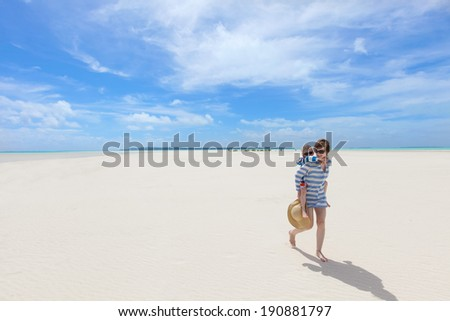 young happy mother giving her son a piggyback ride at the gorgeous tropical beach