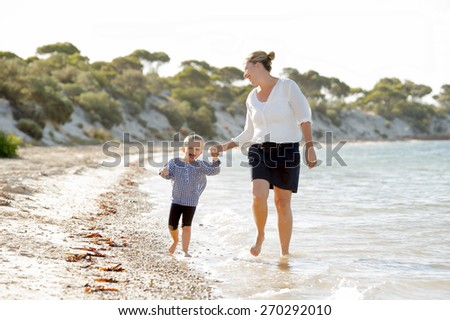 young happy mother holding hand of sweet blond little daughter walking together on sand at beach sea shore enjoying summer holidays playing in family vacation lifestyle concept - stock photo