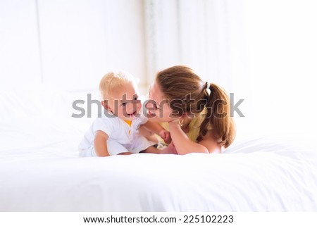 Young happy mother holding her adorable baby, cute blond curly boy, playing in a white bed enjoying a sunny morning in a modern home bedroom