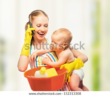 young happy mother is a housewife with a baby does homework and talking on the phone at home - stock photo