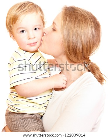 Young happy mother is embracing and kissing her child. - stock photo