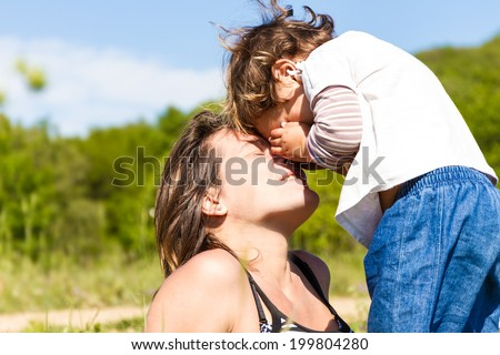 young happy mother playing with her child girl outdoors - stock photo