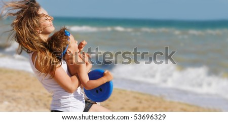 young happy mother playing with son on beach background