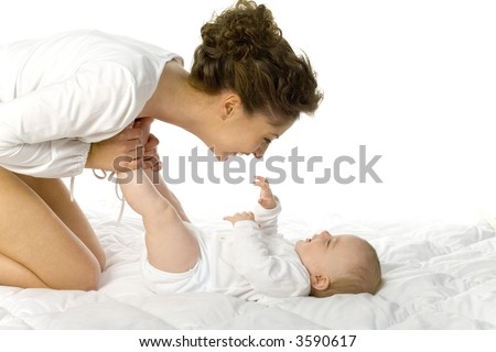 Young happy mother with baby. Woman and baby are lying in bed. Mother is holding baby's legs. White background