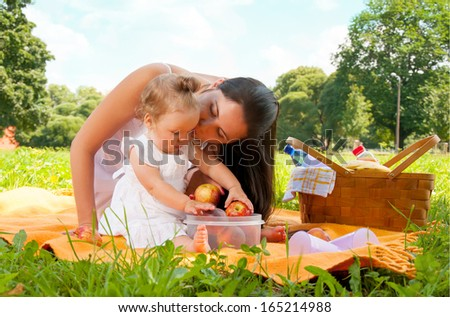 Young happy mother with daughter in the park picnicking - stock photo