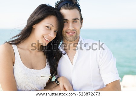 Young happy multi ethnic couple in love at the sea side during a sunny day