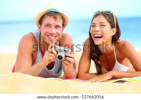 Young happy multicultural couple on beach having fun laughing during summer holiday vacation. Caucasian hipster man with retro vintage camera and asian woman joyful.