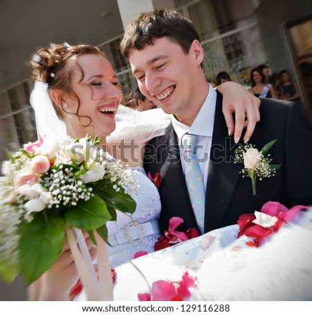 Young happy newlywed couple. Groom holding bride in his arms