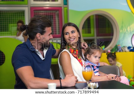 Young happy parents having fun with kids in children playground indoor