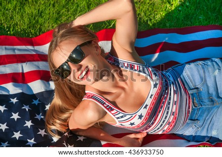 Young happy patriot girl on the american, united states flag - stock photo