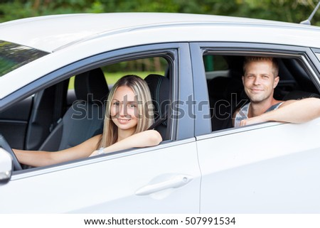 Young happy people enjoying a road trip in the car
