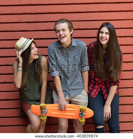 Young happy people posing with penny board against red brick wall. Urban lifestyle, happiness, joy, friends, teenage, first love concept. Image toned and noise added. - stock photo
