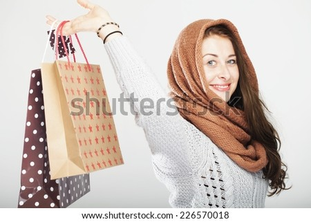 young happy playful cute winter girl with shopping bags, isolated on grey background