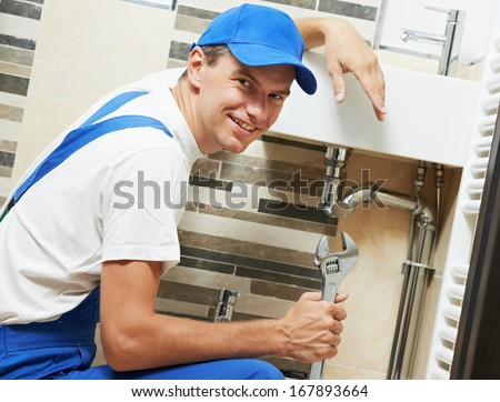 Young happy plumber worker with spanner at sanitary washbasin installation system - stock photo