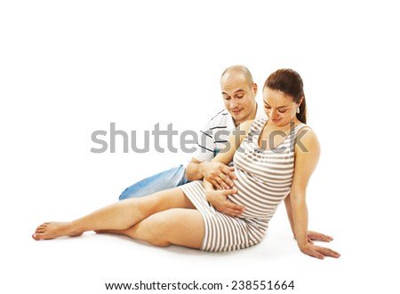 Young Happy pregnant couple sitting on the floor - isolated over a white background - stock photo