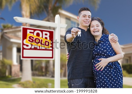 Young Happy Pregnant Hispanic Young Couple with House Keys in Front of Their New Home and Sold For Sale Real Estate Sign. - stock photo