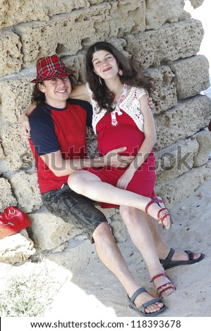 Young happy pregnant woman & her husband in the colored clothes - stock photo