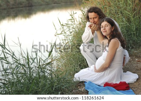 Young happy pregnant woman & her husband in the country clothes - stock photo