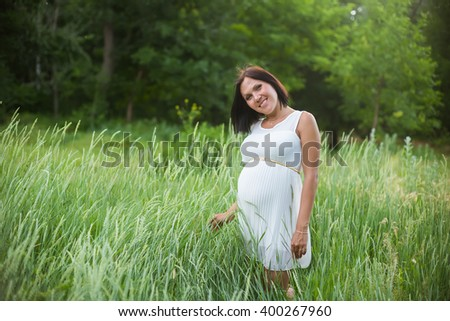Young happy pregnant woman in white dress standing in the field of high green grass. Pregnancy. Parks, outdoors