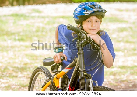 young happy preteen child boy riding a bicycle on natural park background, boy riding a bike in a park