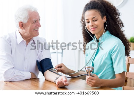 Young happy professional nurse checking senior man's blood pressure