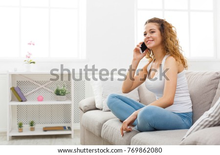 Young happy redhead woman calling on mobile phone sitting on beige couch at home