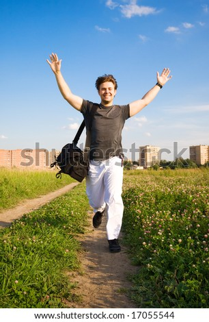 Young happy running man. On summer field background. - stock photo