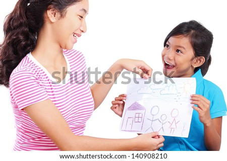 Young happy schoolgirl showing her drawing to a lady. - stock photo