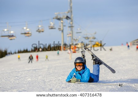 Young happy skier girl in blue ski suit orange goggles and helmet lying on the snow at ski resort on a sunny day. Ski vacation. - stock photo