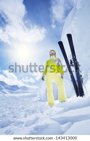 Young happy skier woman standing with ski by huge snowdrift