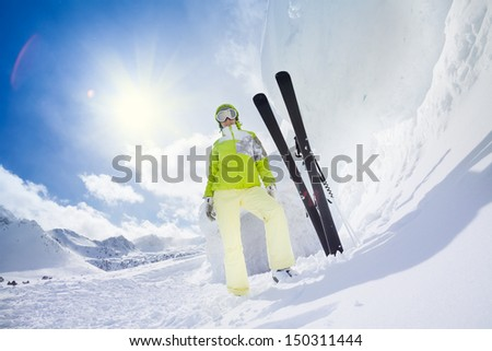 Young happy skier woman standing with ski put in snow huge high snowdrift - stock photo