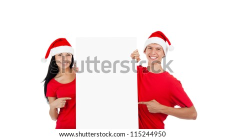 young happy smile couple standing hold pointing finger at a blank board, handsome guy attractive girl wear red shirt santa claus hat, isolated over white background, studio shoot