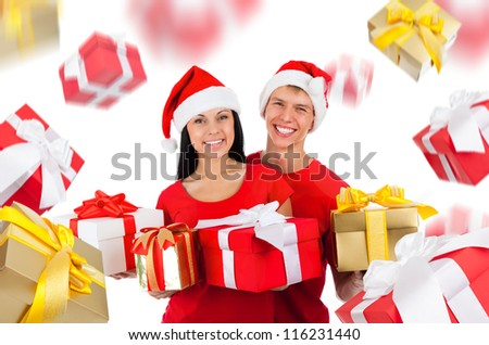 Young happy smile excited couple wear red Christmas hats and shirts, hold gold gift box present, looking at camera, present golden gift box fall fly around isolated over white background - stock photo