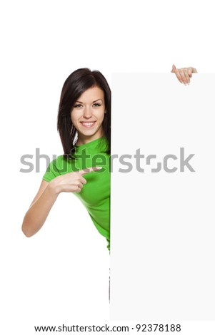 young happy smile woman standing hold pointing her finger at a blank board, attractive girl wear green shirt, isolated over white background, studio shoot - stock photo