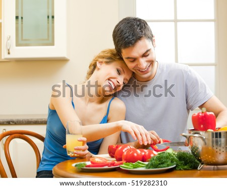 Young happy smiling amorous couple cooking together at home. Love, relations, romantic concept shot.