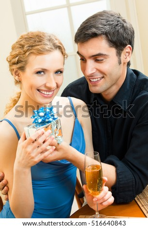 Young happy smiling amorous couple with gift and champagne at home. Love, relations, romantic concept shoot.