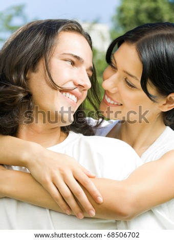 Young happy smiling amorous embracing couple together, outdoor