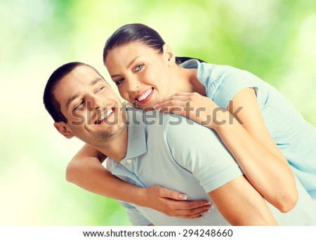 Young happy smiling amorous embracing lovely couple, outdoors