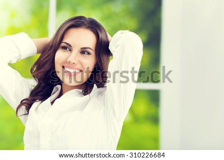Young happy smiling attractive brunette businesswoman with raised arms, at office - stock photo