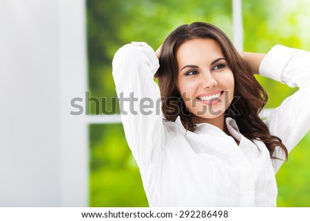 Young happy smiling attractive brunette businesswoman with raised arms, at office, with blank copyspace area for slogan or text - stock photo