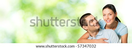 Young happy smiling attractive couple, outdoors. You can use left part for slogan, big text or banner. - stock photo