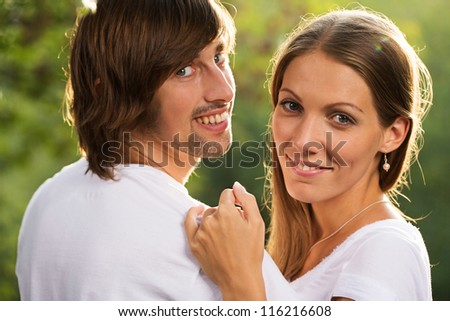 Young happy smiling attractive couple together outdoors - stock photo