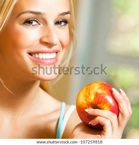 Young happy smiling beautiful blonde woman with apple - stock photo