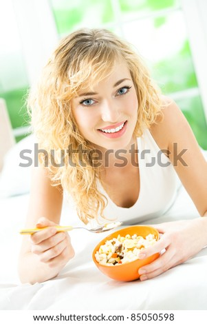 Young happy smiling beautiful woman eating muslin at home