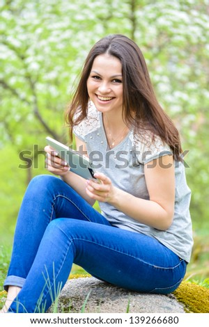 Young happy smiling beautiful woman working on pda or tablet pc in summer outdoors background