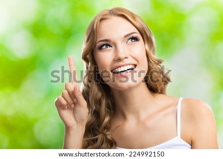 Young happy smiling blond attractive woman, showing one finger or idea gesture, outdoors - stock photo
