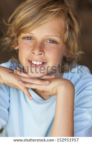 Young happy smiling blond boy child aged about twelve or early teenager resting on his hands