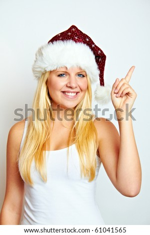 young happy smiling blond christmas woman is showing something - stock photo