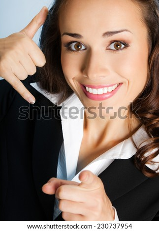 Young happy smiling business woman with call me gesture, over blue background - stock photo